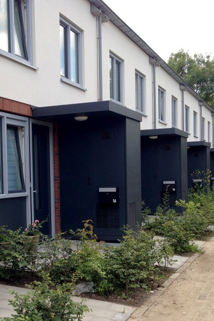 A renovated multifamily housing building with exterior mechanical rooms. The Energiesprong program retrofits often include new landscaping.