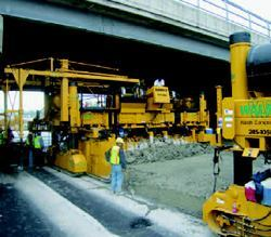 As the paver passed under each bridge, it was locked on a cross slope and the gantry was drawn in, allowing the slip-forming to continue.
