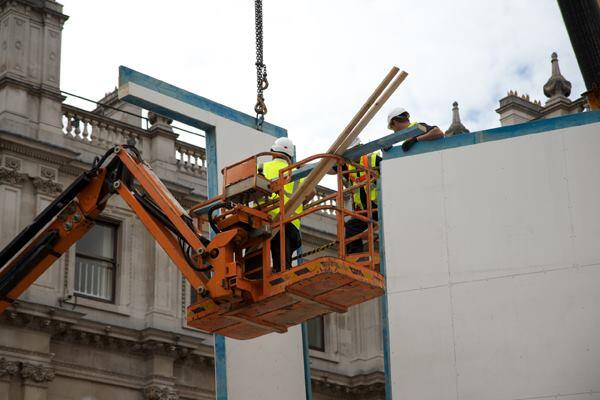 Workers lift in the structural walls for the Homeshell installation at the Royal Academy of Arts in London.