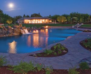The project featured a 6000-square-foot, dry-shotcrete pool and a rock-patterned  stamped concrete deck with integral colored concrete and dry-shake hardener  accents. The pool cabana is in the background.