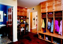 Remodeler John Sylvestre designed this mudroom with custom-made pieces including lockers, boot storage, and a desk. The mudroom is open to the living area, so the homeowners chose a furniture finish for the cabinetry.