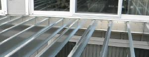 Figure 5. Attach the steel ledger to the house as you would a wood one, with 1/2-inch lag bolts and standard flashing details.