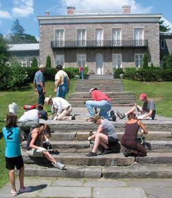 Members of the Heritage Conservation Network repair the stone walkways at the Bartow-Pell Mansion Museum.