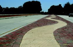 Decorative pavers in the Weems Creek Bridge  median form a serpentine design representing a meandering creek. Water  runoff drains to the middle of the median for collection. The 15-foot-wide  median can be removed if necessary in the future to provide additional capacity. Photos: KCI  Technologies Inc.