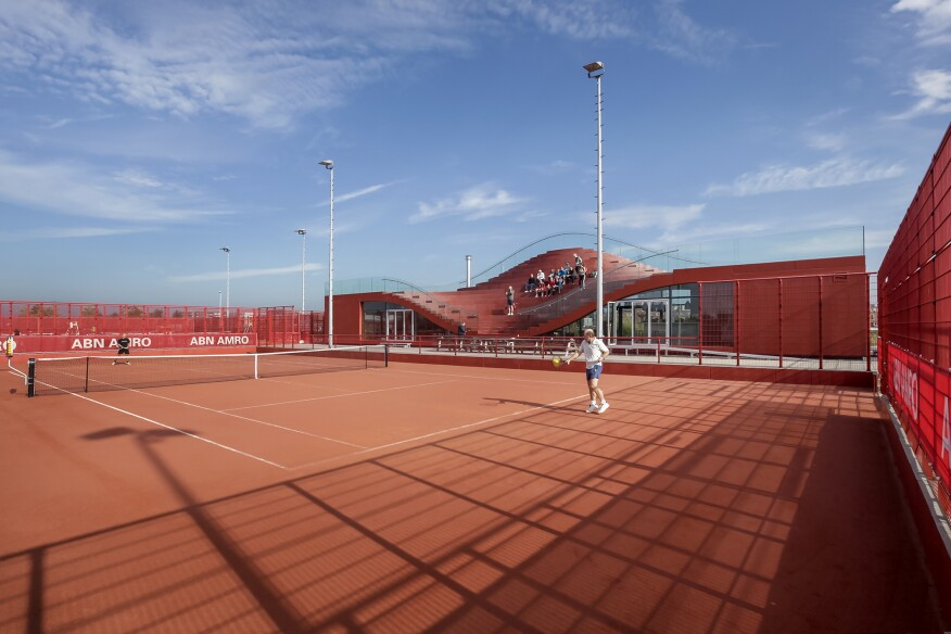 From the exterior of the clubhouse, to the metal fences dividing the clay tennis courts, red wholly dominates this site.