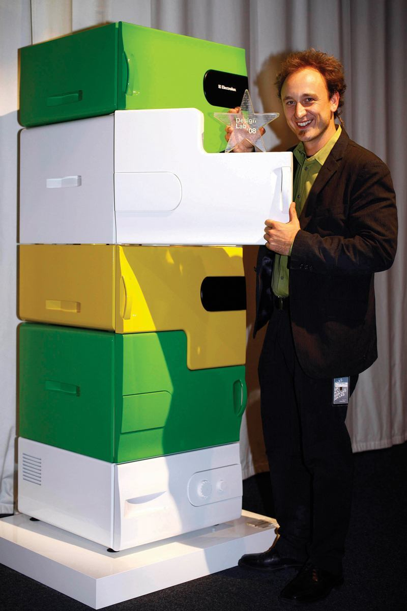 """Electrolux Design Lab 2008 winner Stefan Buchberger displays the Flatshare refrigerator, which has separate drawers for each user. Individual users can personalize their drawer with a colorful """"skin."""""""