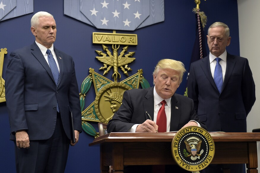 President Donald Trump signs the executive order at the Pentagon on Jan. 27.