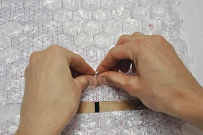 To help visualize the three-dimensional quality of the surface, the team went through a prototyping process that involved popping bubble wrap over a pattern of planned raised, flat, and depressed dots.