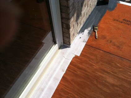 After flashing the joint between the deck and the wall with aluminum, the author sealed the metal flashing to the plywood with selfadhesive seam tape.