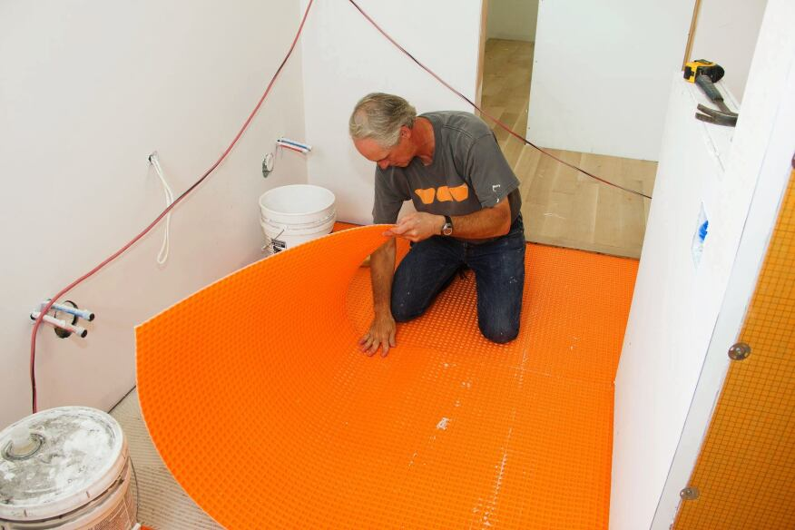 Tile contractor Tom Boucher of Integrity Tile, based in Kennebunk, Maine,  lowers a piece of Schluter Ditra decoupling membrane into a mortar bed to serve as underlayment for a custom marble tile floor in the master bathroom for a new house under construction next to the ocean south of Portland, Maine.