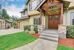 Luxurious home with well kept lawn, and green exterior paint.