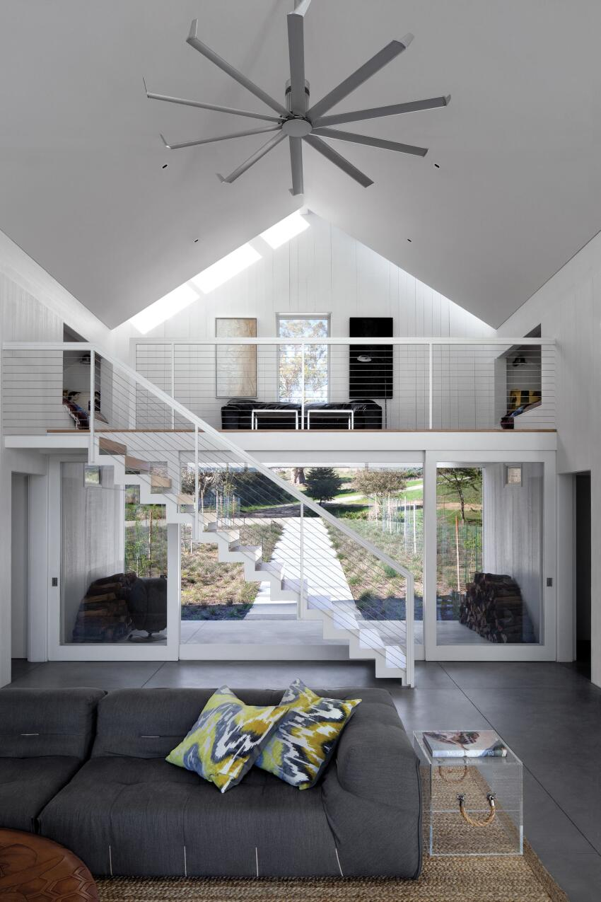 The double-height central living room is the core of the house, and a loft over the entry porch allows for a bilevel gathering. The 4-inch-thick concrete floors of the ground level give way to salvaged white oak from Restoration Timber on the stair treads and loft floor above.