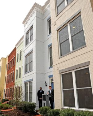 "Brian ""A.J."" Jackson, vice president of land acquisition and development for EYA, and Courtney Baker, of USGBC's Residential Market Development team, speak in front of the Capitol Quarter townhomes during the Earth Day certification ceremony."