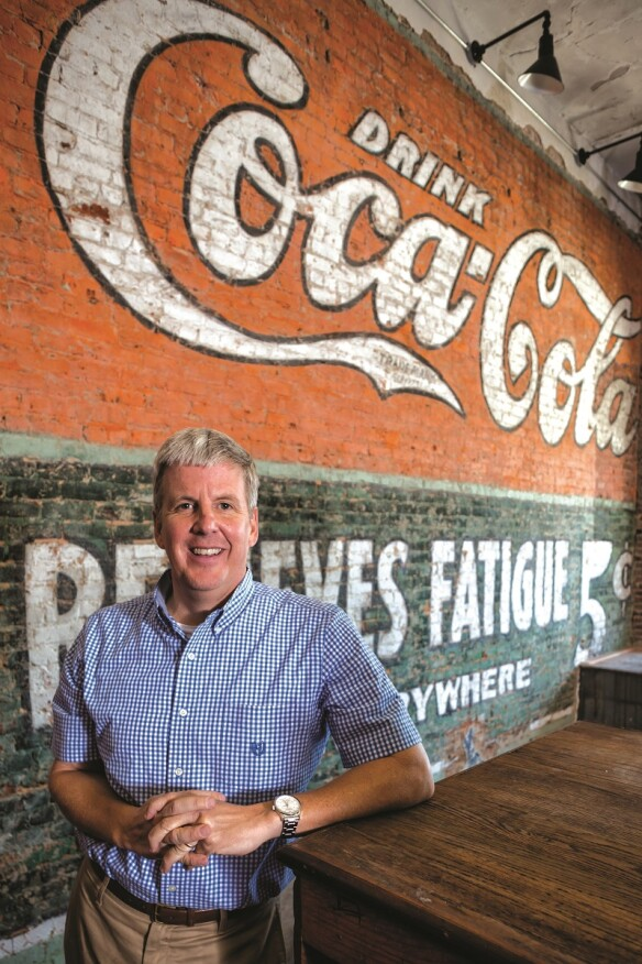 Dozier Smith T, member of the Opelika City Council and owner of Smith T Hardware, with a 100-year-old Coca-Cola mural he uncovered in his store in August 2014