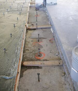 Anchor bolts were installed to provide additional support for new concrete in this floor slab. Center section shows the original floor; left section shows the cellular concrete layer; finish layer of normal-weight concrete is visible at right.