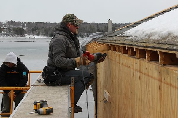 Carpenter Dan Armstrong cuts the eaves off the roof of an existing home in Newcastle, Maine.