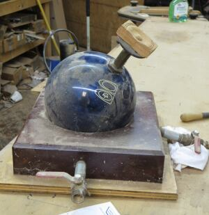 The bowling ball clamp is a simple but clever fixture that cost almost nothing to make. When the device is in use the pipes in the base (the one on the right is sitting loose) are connected to stiff hoses that lead to a vacuum pump. When a vacuum is applied it holds the bowling ball tight to the base and the work piece tight to the block on top of the pipe coming out of the ball. The work piece can be removed or the ball repositioned by turning off the pump or closing the valves on the outlet pipes.