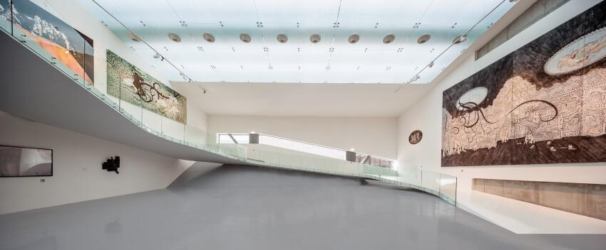 Continuing the flow motif, an elliptical ramp emerges from the exhibit hall's first level and gently curves up to the mezzanine, which houses more paintings and a video art collection.