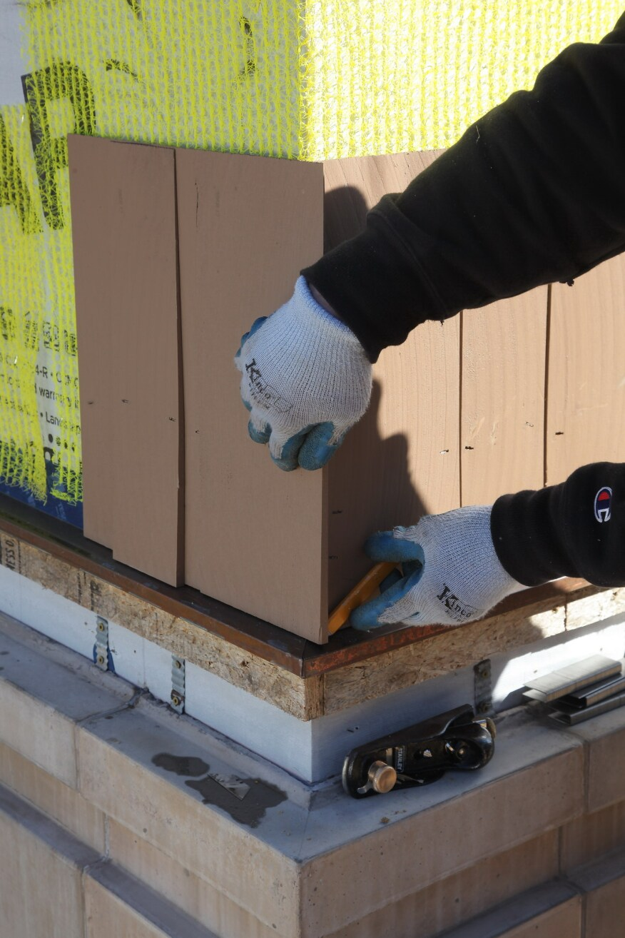 For the corner shingle on the adjacent wall, hold the shingle in place and scribe along the edge of the first shingle. Trim it to fit as before and then nail it into place.