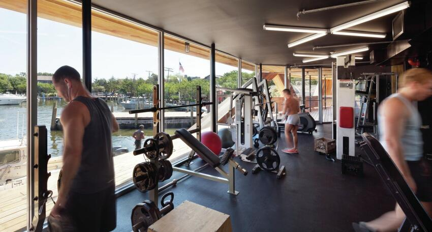The gymnasium's floor-to-ceiling windows provide ample daylight while allowing patrons to look out over the harbor.