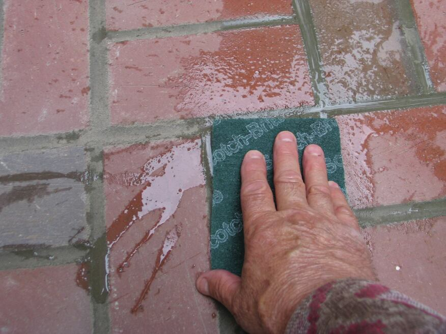 Scotch-Brite scouring pads (green synthetic steel wool pads) and water was used to scrub the bricks around the edges. By working carefully and timing things right, the author was able to avoid the use of chemical cleaners.