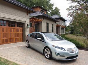 "The Chevrolet Volt extended range electric vehicle with a 230 miles-per-gallon rating, is shown in front of the GreenHouse, a custom-built 4,000 sq-ft ""carbon neutral"" house in MacLean, Virginia Tuesday, September 22, 2009. The Volt will travel 40 miles on a single charge, meaning it could drive to Washington, DC and back twice from this location, without using a drop of gas. GreenHouse was designed and constructed using the latest environmental technologies, including solar hot water and electricity, a green roof system, rain water capture, geothermal heating/cooling and much more. The house will be open to the public for tours October 10-30. (Photo by Mark Finkenstaedt for General Motors)"