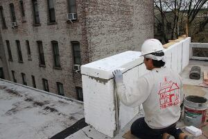 A carpenter from J's Custom Contracting details the foam insulation for a Sto exterior insulated finish system (EIFS) cladding on the parapet wall of a Passive House addition in Brooklyn, New York. The foam will be covered in wire mesh reinforcement and cement, along with additional flashing and roofing details to shed wate.