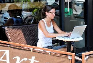 A woman works on her laptop from the comfort of a sidewalk cafe.