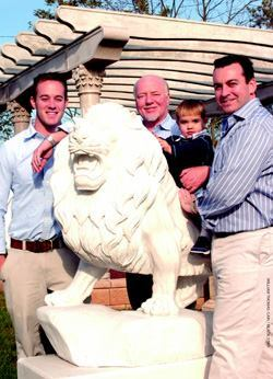Three generations of Creter Vault Corp.: left to right, son Matt; his father, Dick; 2-year-old  Sean Richard; and his father, Rich, stand among the company's  out door granite sculptures.
