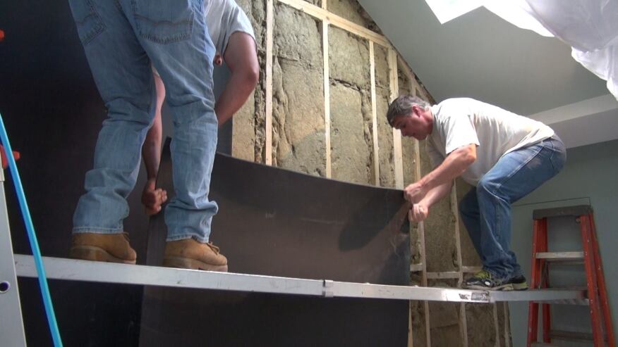 A crew from New England Soundproofing applies a sound-deadening, mass-loaded, sheet vinyl product called Sound Barrier HD to a party wall separating a condo stairwell from the unit next door. Materials like this vinyl and the special sound-absorbing rock-wool fiber insulation in the wall cavities can be used to absorb, deaden, and muffle sound vibrations from a variety of sources. Solutions are based on the nature of the sound source and the subjective perceptions of building occupants.