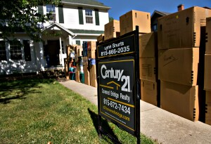 Moving boxes sit stacked near a Century 21 Real Estate LLC for sale sign outside of a home in Princeton, Illinois, U.S., on Wednesday, May 30, 2012. The number of Americans signing contracts to buy previously-owned homes fell in April by the most in a year, indicating the U.S. housing recovery remains uneven. Photographer: Daniel Acker/Bloomberg