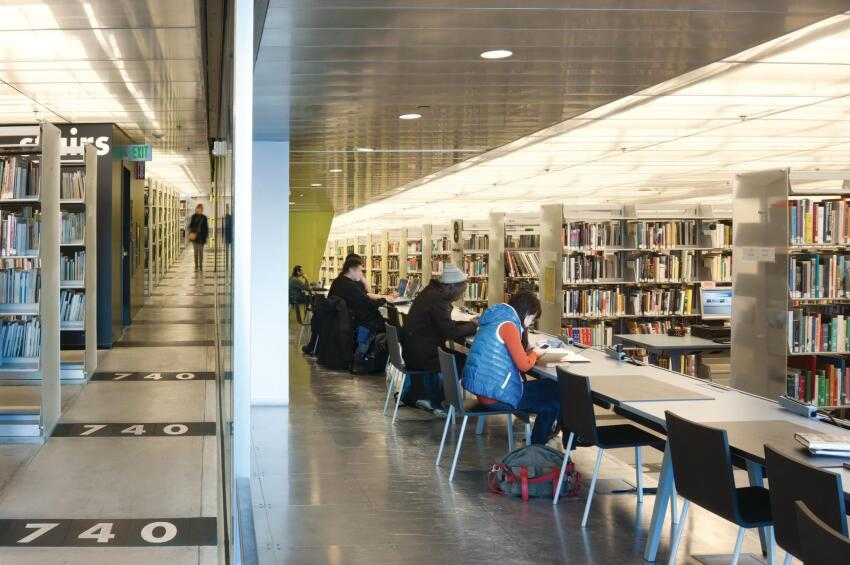 In OMA's library, patrons gather at a table amid the book spiral, which connects four floors of bookstacks via gently sloped ramps. Dewey decimal numbers are noted on the floor.