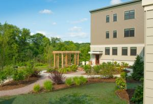 The property features an outdoor garden with a sitting area and a walking path for residents.