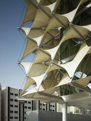 To avoid turning the glass building into a greenhouse, Gerber left a 2-meter air cavity behind the tensile fabric façade.