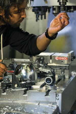 A worker changes the tool on the spindle of Edison Price's Haas Automation VF-1 vertical machining center, which CNC-mills metal parts that are used in the final assembly of the company's track fixtures.