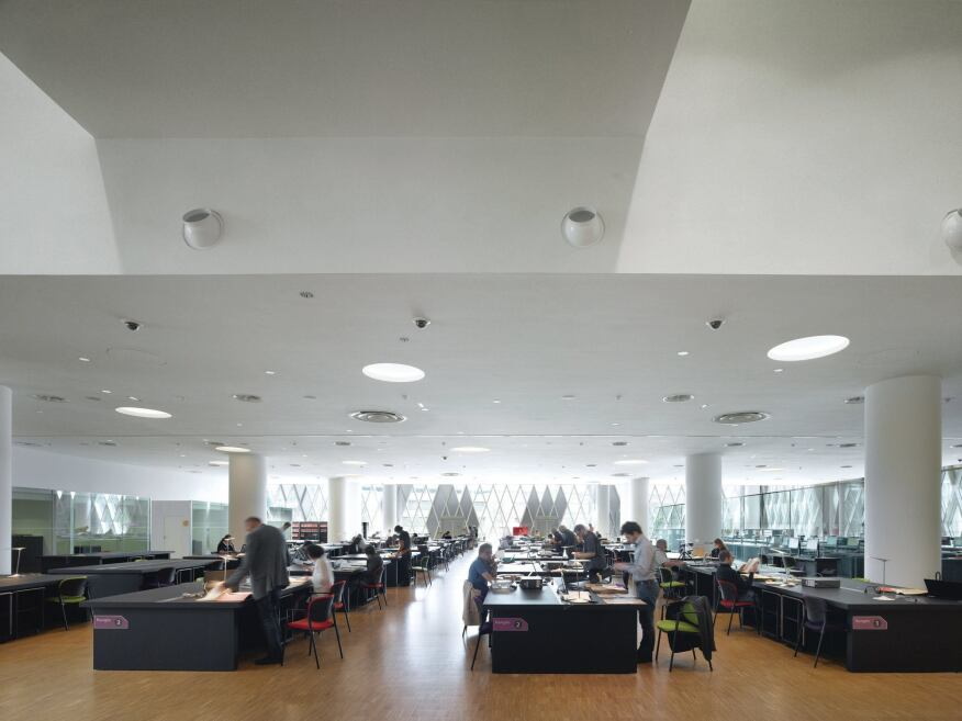 The ground-floor reading room features rows of black tables, where scholars can view archival material.