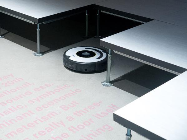 A Roomba vacuum cleaner lies under a raised floor. The vacuum uses sensors to map a room and autonomously navigate the space while cleaning.