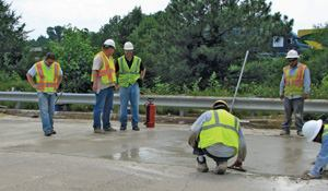 Workers stand on the newly placed concrete only 30 minutes after they made the repairs.
