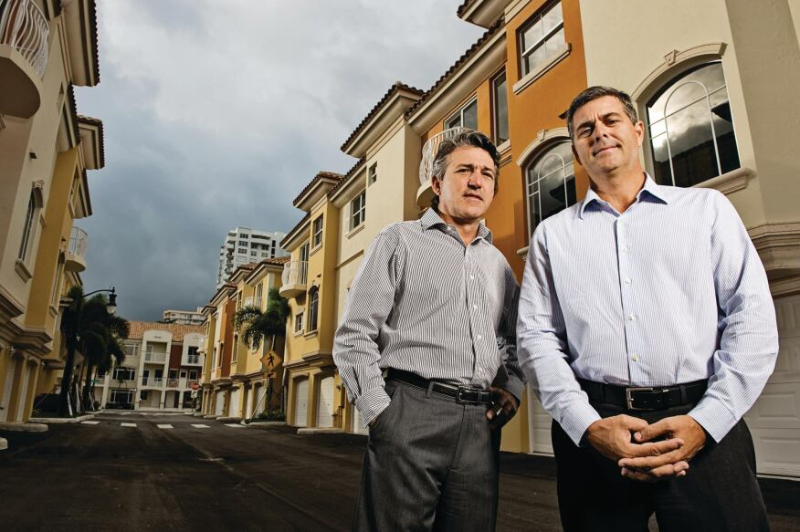Frank Mackle (far right) and Venny Torre of Torre Mackle Group, standing in front of Terzetto Villas, a townhouse project in Miami they built out for Ocean Bank, which provided construction financing.