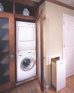 The stackable washer/dryer cabinet and in-wall laundry hamper are part of an elaborate built-in dressing room in a master suite expansion.