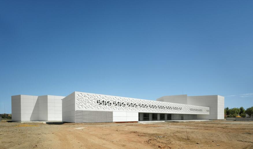 Polygonal perforations, abstracted from the building's hexagon-based design, cascade across the exterior of the Contemporary Art Center in Córdoba, Spain, allowing natural light to dapple its interior.