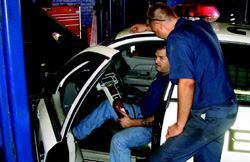 "Scott Suter (seated) and James Pounds, both automotive mechanics in Omaha, Neb., use  a Rotunda scanner from Ford Motor Co. to diagnose the reason behind  a ""check engine"" light on a police squad car. Photo: City of  Omaha"