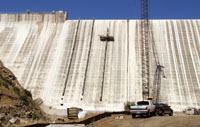 Concrete is removed on the dry side of the dam by a customized robot that moves up and down along mast sections.
