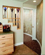 An open-paneled stairwell and a curved wall make this basement entry less confining.