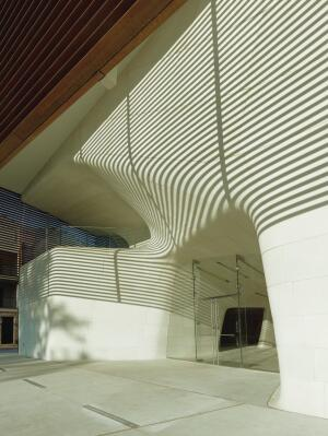 Entrance under the copper-slat canopy.