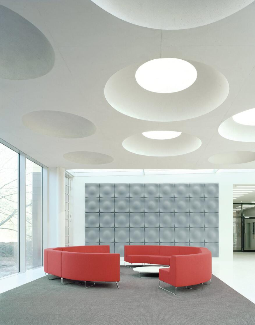 """In a second-floor lounge next to the student café, carpet from Forbo helps soak up even more noise. The architects knew that acoustics would be a concern in a largely open interior of glass, terrazzo, and concrete. """"But when you have a gathering of 300 people, clothes [absorb a lot of noise],"""" Piotrowski says. And the clients are comfortable with the fact that the addition still requires some fine-tuning. """"They understand that having a brand new building, the first in 40 years, takes a little getting used to,"""" he says, so it's not a process that they are accustomed to. But it is one that is welcome: """"They have a little influence,"""" Ecker says."""