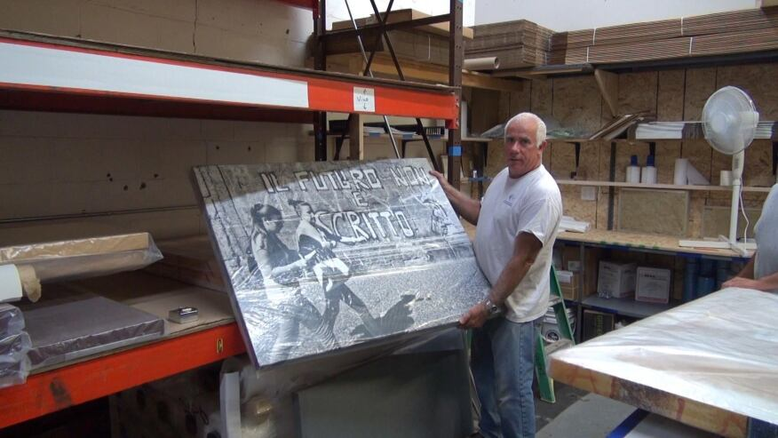 "Joseph Drago of New England Soundproofing holds a finished ""REVRB"" noise-absorbing panel with a screen-printed art surface at his company's Waltham, Massachusetts, shop."