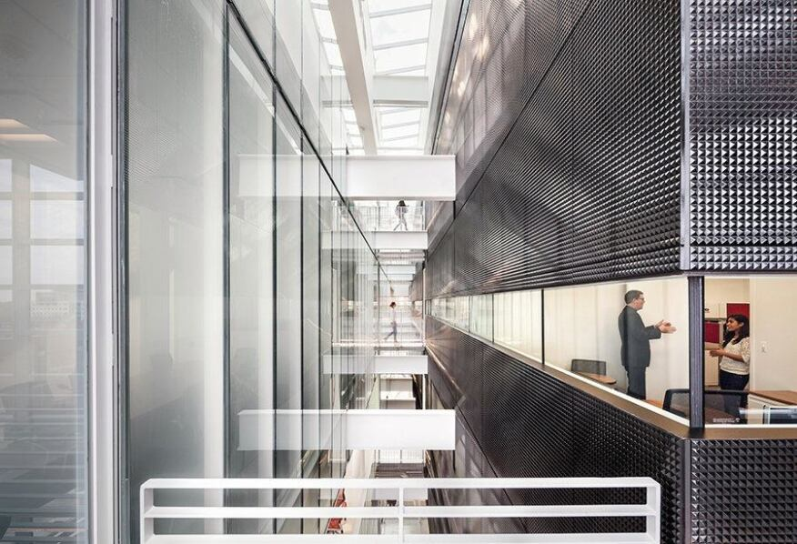 Bridges and structure cross the interstitial spaces between perimeter breakout spaces and interior offices and classrooms.
