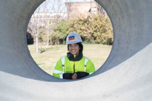 Angkita Podder, DDC's Civil Engineering Intern on the project, peers through a section of 42-inch reinforced concrete storm sewer, one of many being installed along College Place.