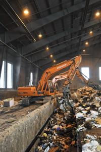 "Trash is delivered to the Tinker Creek Transfer Station via refuse trucks and loaded onto railcars situated belo0w the main receiving platform of the transfer station (pictured). The ""Waste Line Express"" - a custom-built train operated by Norfolk Southern Railroad - then transports the more than 700 tons of waste gathered from the residents and businesses each day from the transfer station to the landfill, a 33-mile one-way journey."